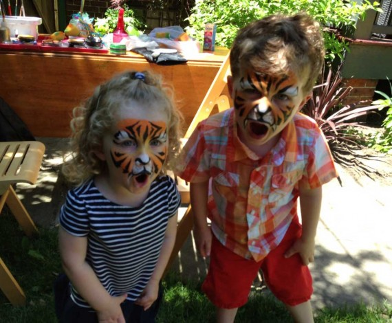 Two kids with tiger face paint roaring to the camera