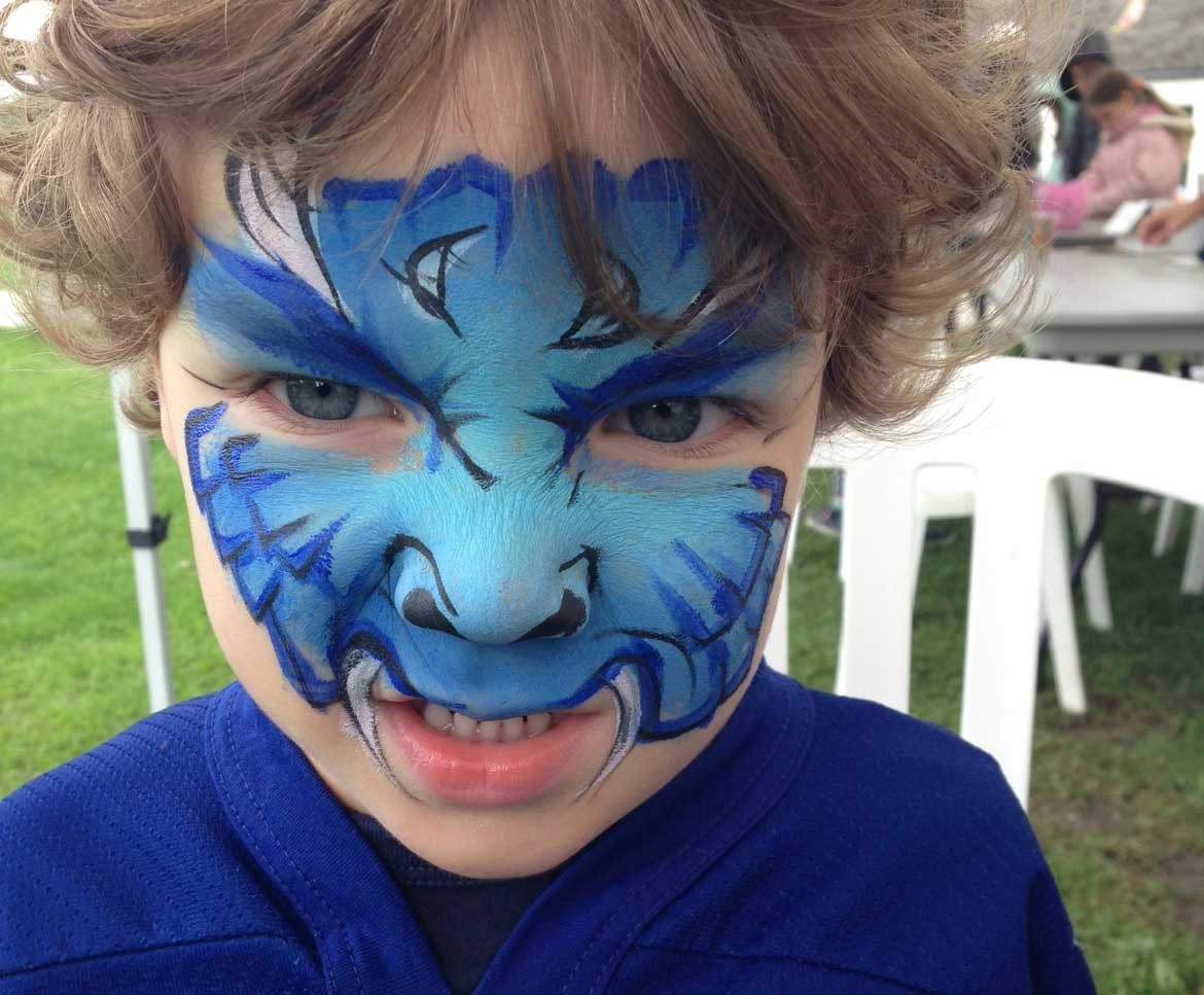 Little boy looking angrily at camera with blue monster face paint
