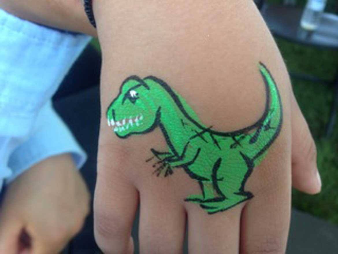 Light green tyrannosaurus rex dinosaur body art on child's hand