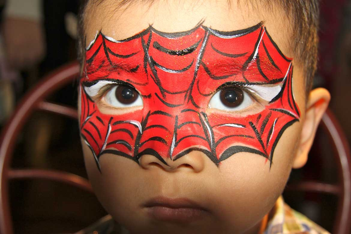 Boy with Spiderman face paint looking at camera