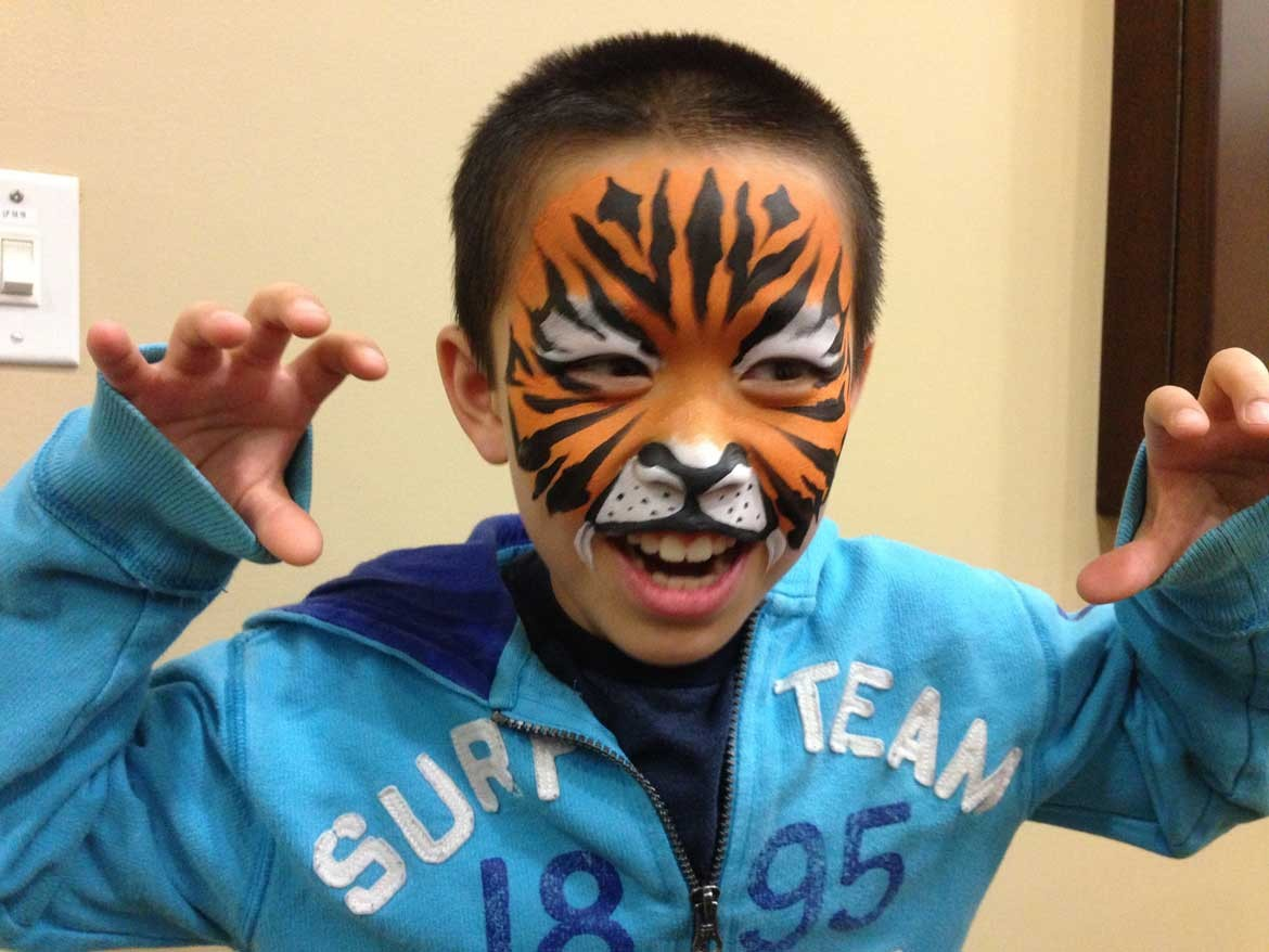 Child with tiger face painting roaring to camera