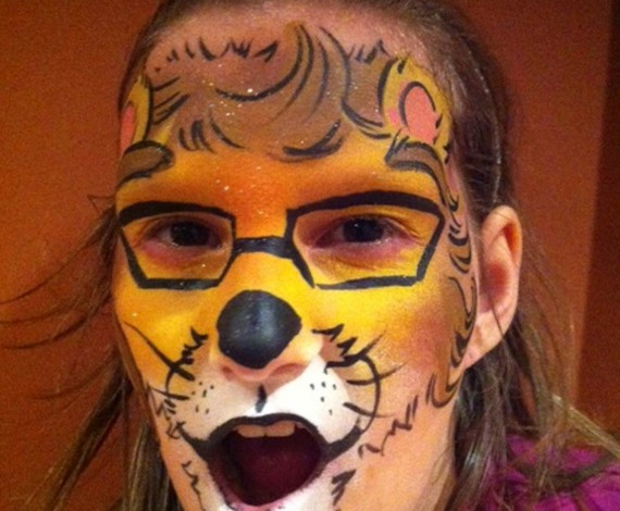 Woman roaring at camera with her face painted like a bear
