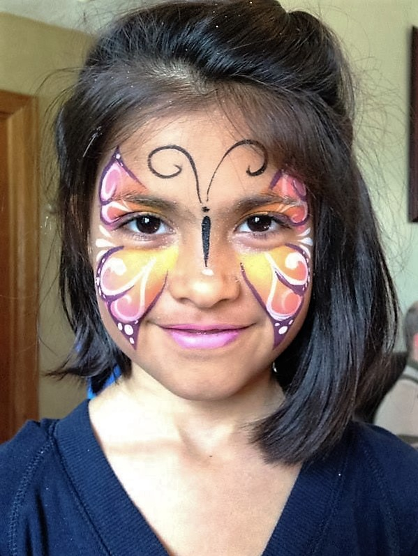 Little girl smiling at camera with colourful butterfly face paint