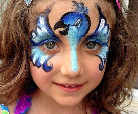 Little girl smiling at camera with blue happy bird face painting design