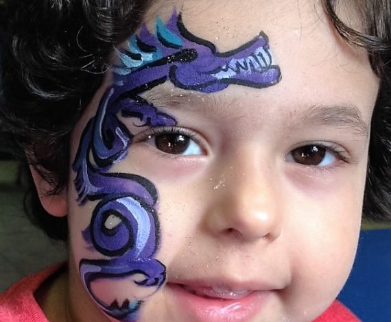 Little boy smiling at camera with purple dragon face paint