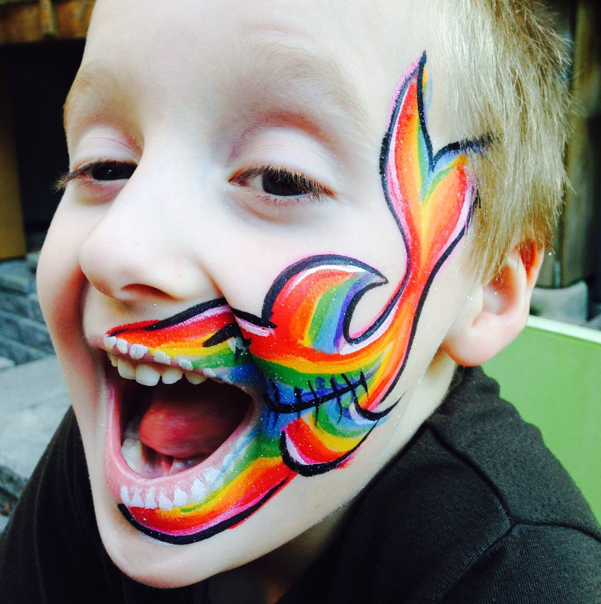 Rainbow shark drawn on little boy's cheek