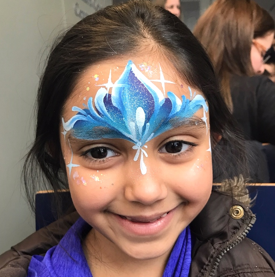 Blue, sparkly princess crown painted on child's forehead