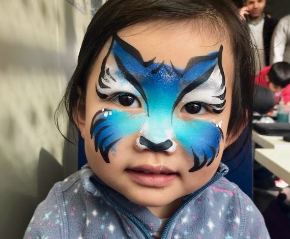 Blue wolf design painted on child's face