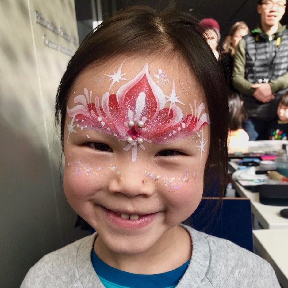 Pink, sparkly princess crown painted on child's forehead