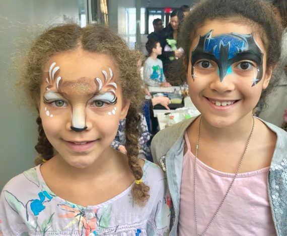 Girl with Face paint to look like deer next to another girl with batman symbol face painted on.