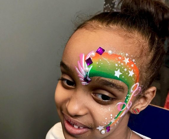 Beautiful sparkly rainbow painted across half of a girl's face