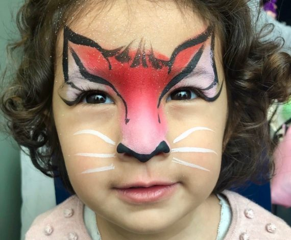Red and Pink cat design painted on child's face