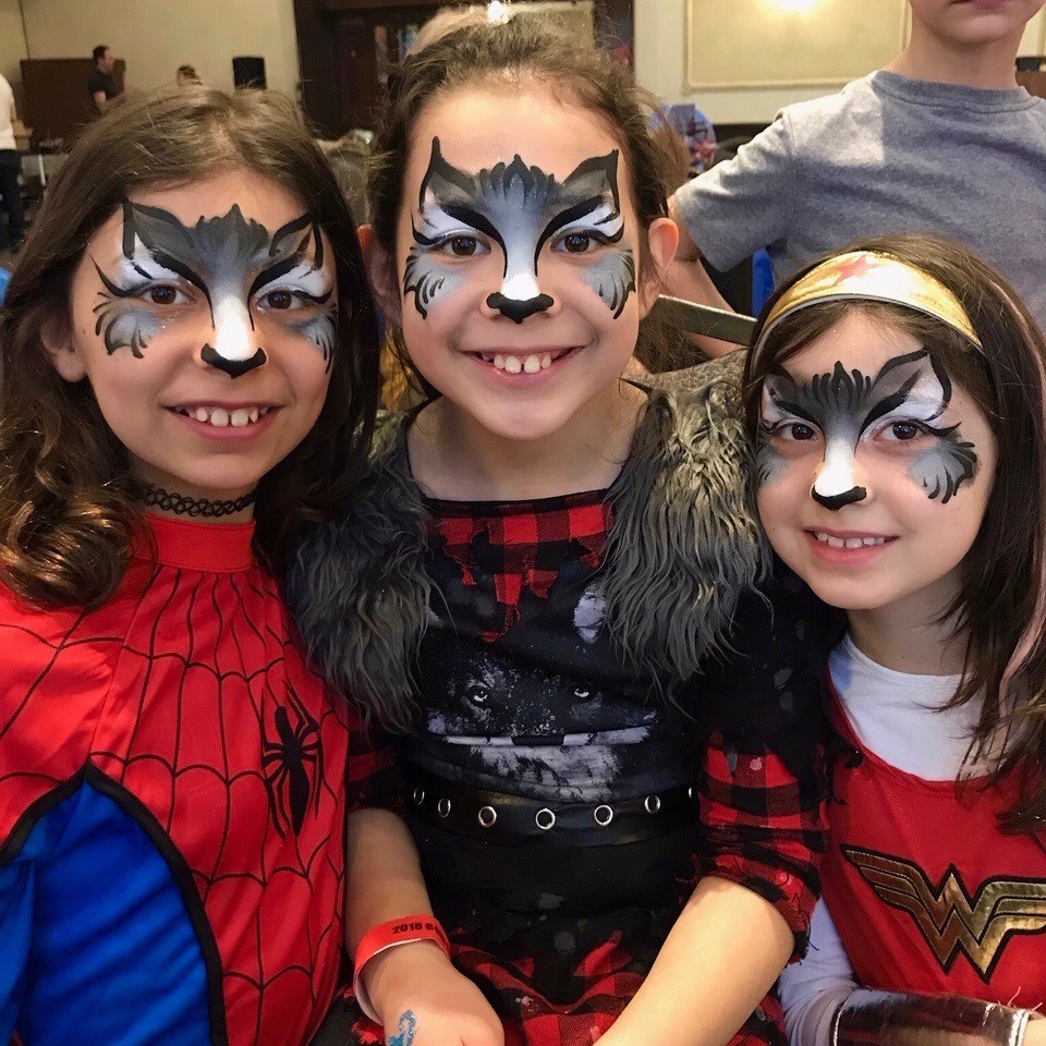 Children's face painting grey wolf example on three girls