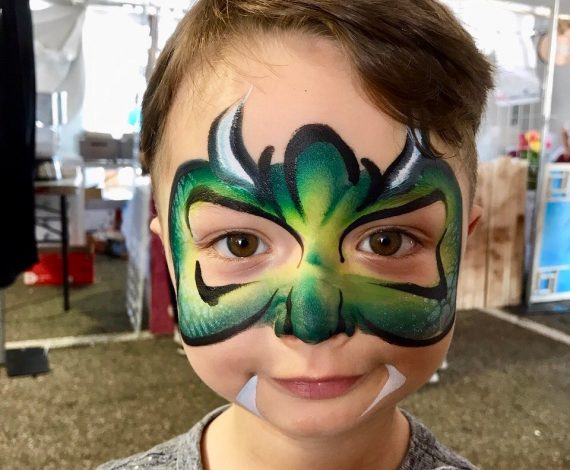 Child with green monster face painting example