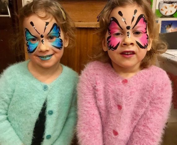 Matching Pink and Blue butter fly face painting on twin girls
