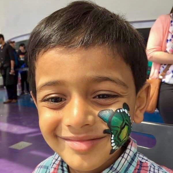 Green turtle painted on boy's cheek