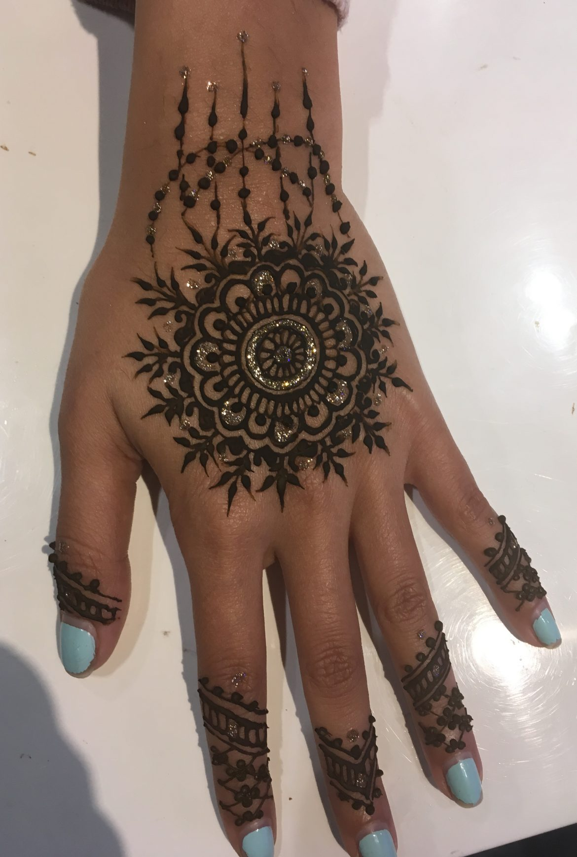 Beautiful sparkle henna on back of hand with more intricate patterns on fingers