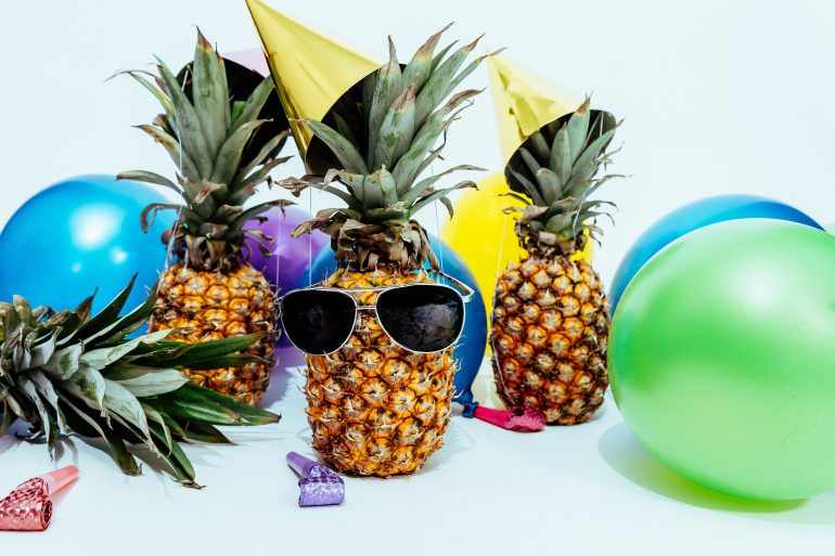 Pineapple wearing sunglasses, surrounded by beach balls