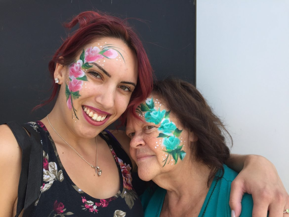 Pink flower painted on woman's cheek next to blue flower's painted on a second woman's cheek