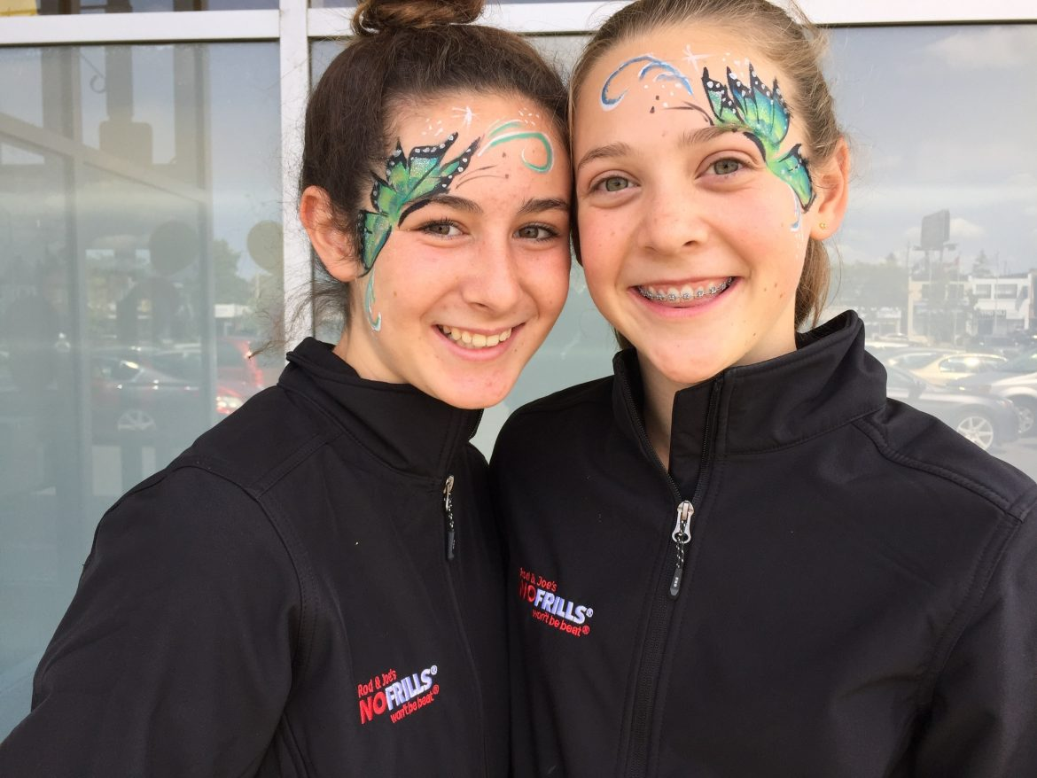 Matching green butterfly painted on two teenagers' faces