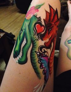 Green dragon, red dragon, and colourful butterfly drawn on a woman's forearm