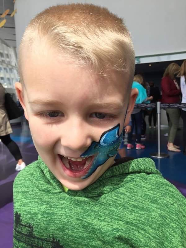 Child with shark painted on his cheek