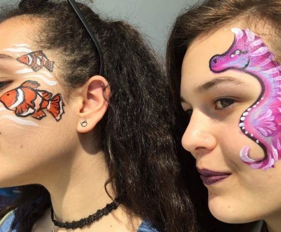 School of clown wish on one girl's face, next to pink sea horse on another girl's face