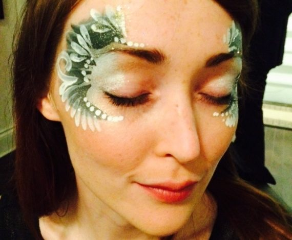 Green intricate designs painted on a woman's face