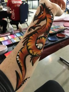 Intricate dragon painted on a woman's forearm