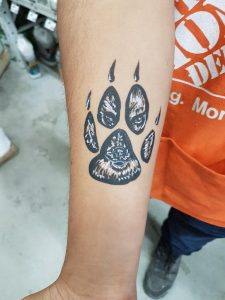 Animal paw print with the face of the animal in the print on a man's forearm