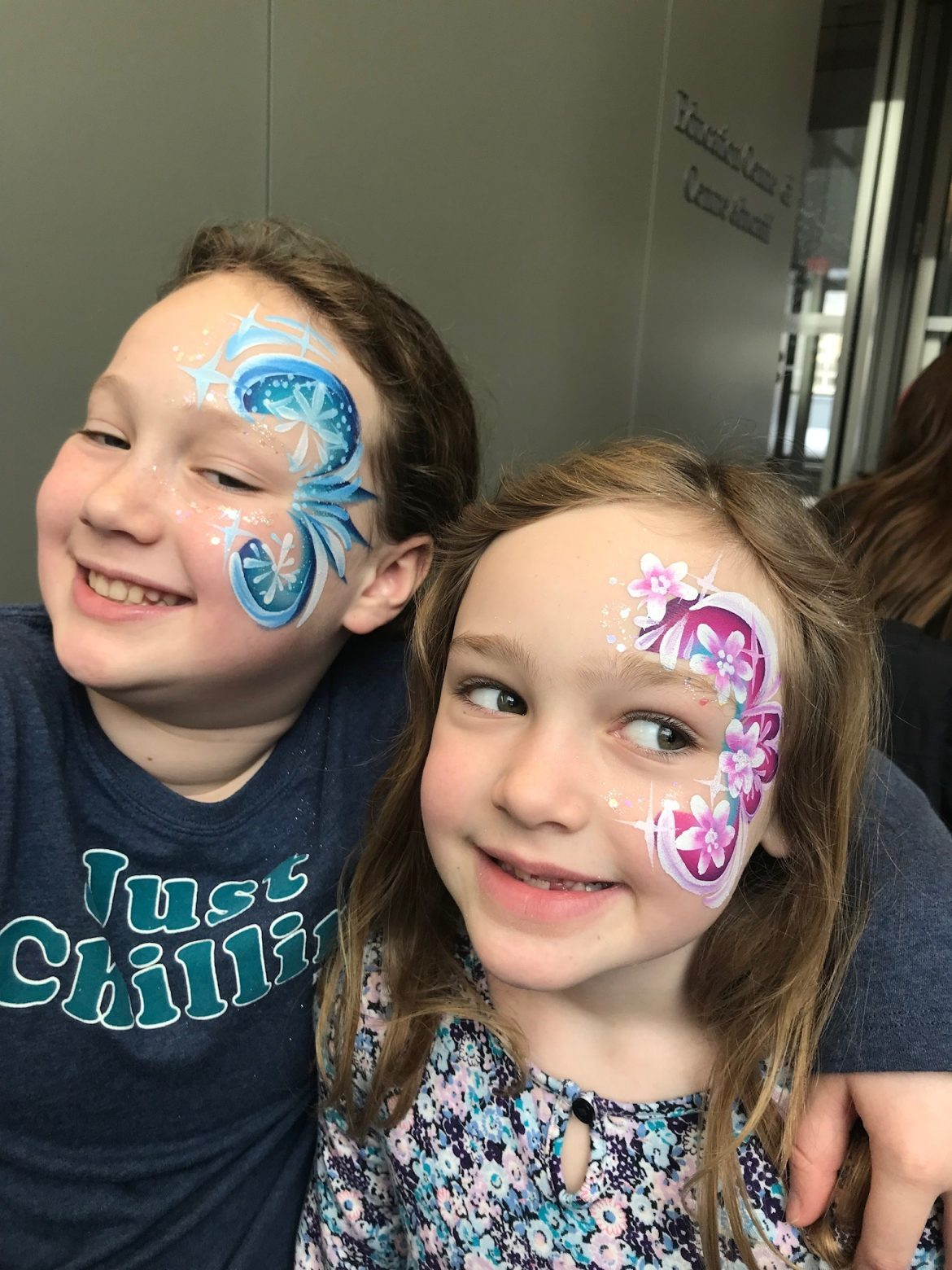 Blue and pink designs painted on children's faces
