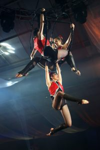 Circus performers hanging from a hula hoop